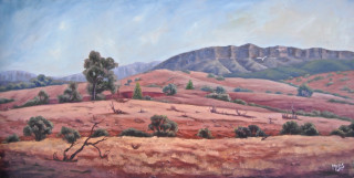 An Oil painting by Moyra Le Blanc Smith in the Realist Impressionist style  depicting Landscape Mountains and Rural with main colour being Ochre Orange and Purple and titled Flinders Ranges View