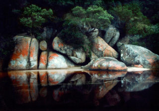 A  photograph by Roz McQuillan depicting River and Rocks with main colour being Black Green and Orange and titled Tidal River Reflection, Wilson's Promontory